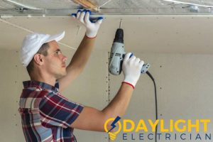 man-drilling-ceiling-downlight-replacement-daylight-electrician-singapore